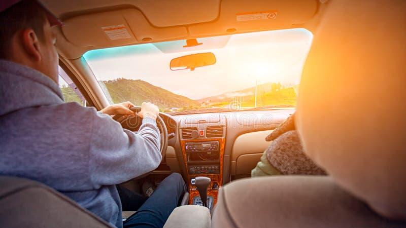 Närbild av ett ungt par av vänner som rider en bil royaltyfri bild