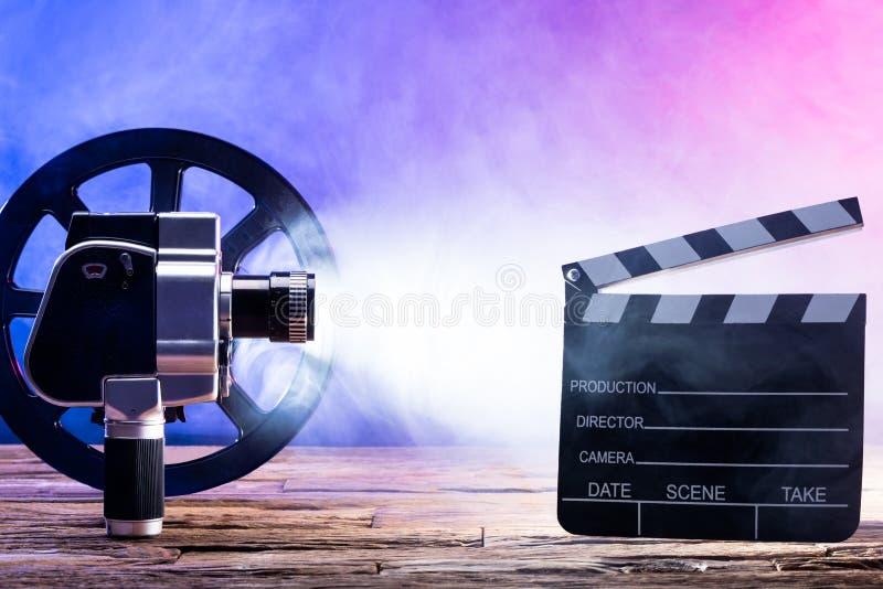 Närbild av filmkameran med filmrullen och Clapperbrädet arkivbild