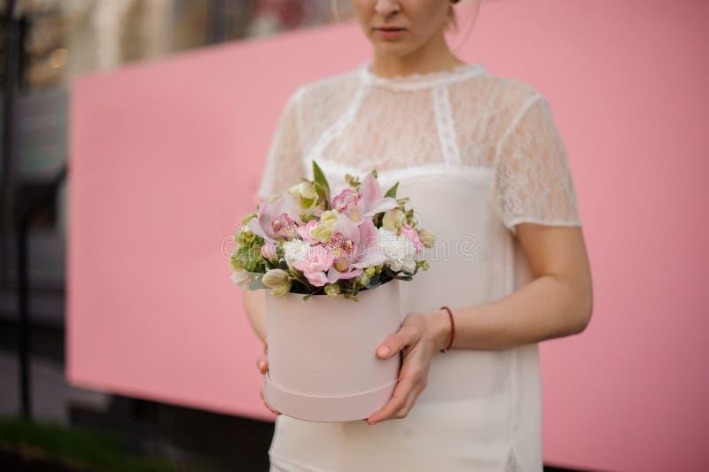 Närbild av flickainnehavbuketten i rosa hattask fotografering för bildbyråer