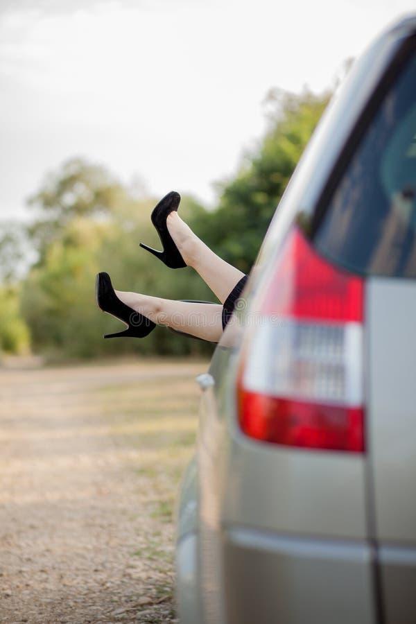Närbild av fot med svarta skor på höga häl av den attraktiva flickan Hon s?tter henne ben till och med f?nstret av modern transpo arkivbild