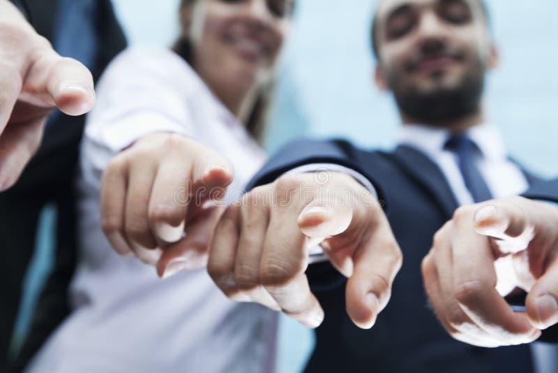 Närbild av fyra affärsfolks fingrar som pekar på kameran royaltyfria bilder