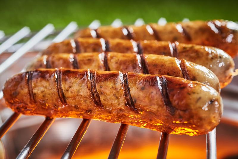 Närbild av fyra lagade mat grisköttkorvar på ett galler royaltyfri foto