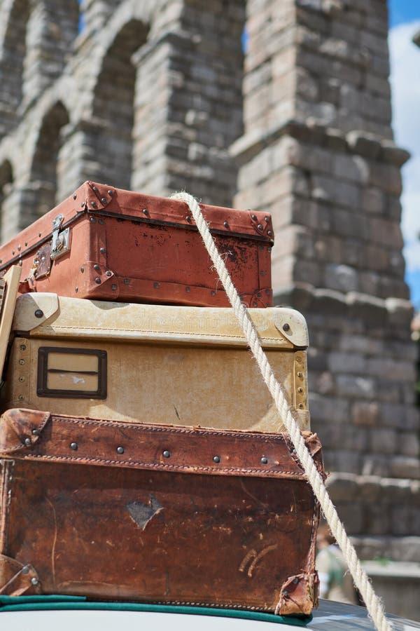 Närbild av gamla tappningloppresväskor som är fästa till taket av en bil med ett rep och i bakgrunden akvedukten av Segovia, royaltyfria foton