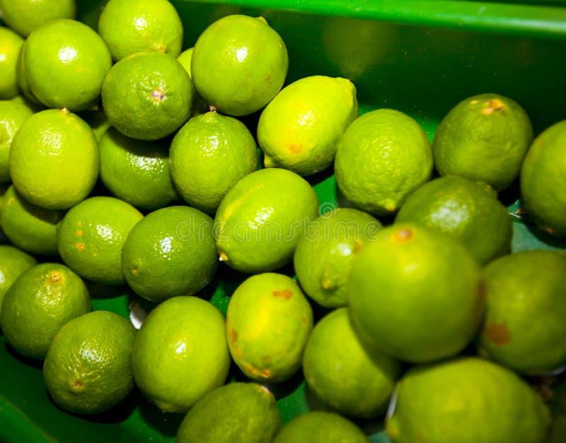 Närbild av gröna citroner på skärm i livsmedelsbutik arkivbild