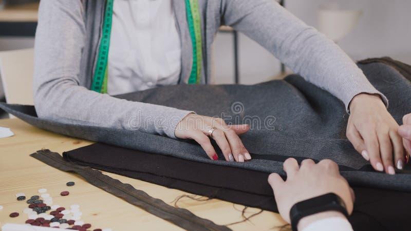 Närbild av händer av anpassade modeformgivare som arbetar med material, dem sammanträde på den härliga atelieren med royaltyfri foto
