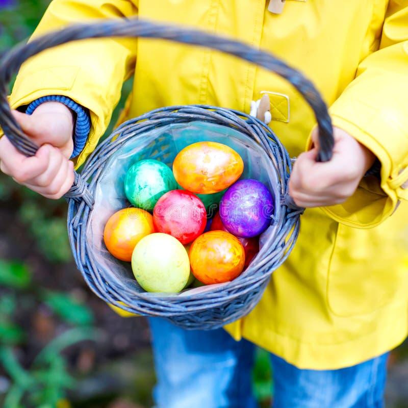 Närbild av händer av det lilla barnet med färgrika påskägg i korg Unge som gör ett ägg att jaga barn som söker och arkivfoton