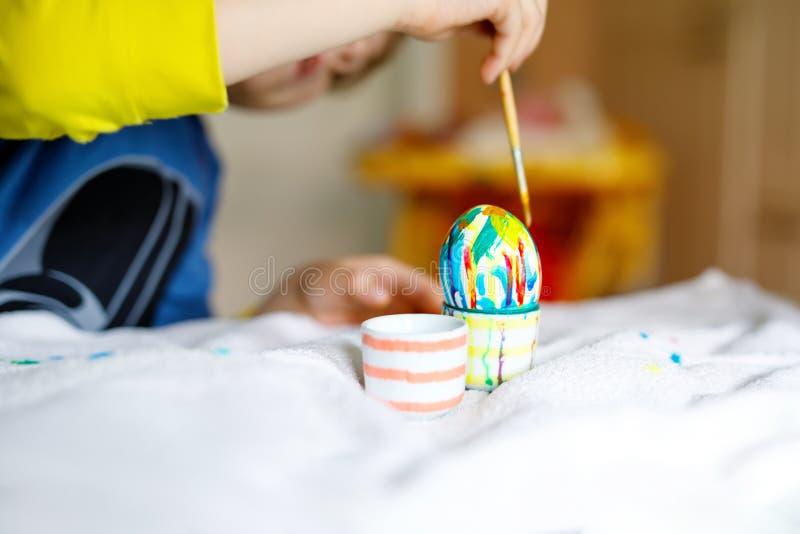 Närbild av händer för liten unge som färgar ägg för påskferie arkivfoton