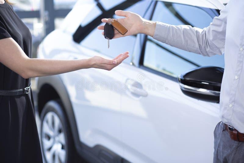 Närbild av händer för säljare` s med tangenter och köparen efter transaktion i bilvisningslokal royaltyfri bild