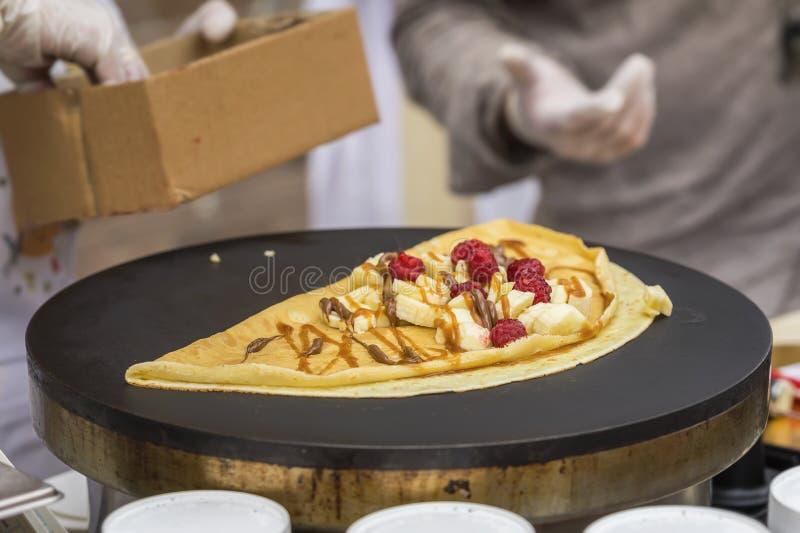 Närbild av händer av kocken i handskar som förbereder den guld- kräppen, pannkaka på stekpannan med den nya bananen, hallon, söts arkivbild