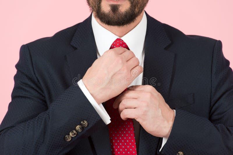 Närbild av händer som justerar det röda bandet på den vita skjortan Affärsmannen i svart dräkt binder ett rött band täta händer u royaltyfri foto