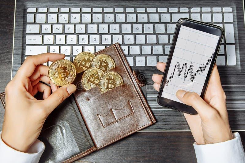 Närbild av händer som rymmer en bitcoin och en smartphone för guld- mynt med ett schema Världsomspännande cryptocurrency och digi arkivbilder