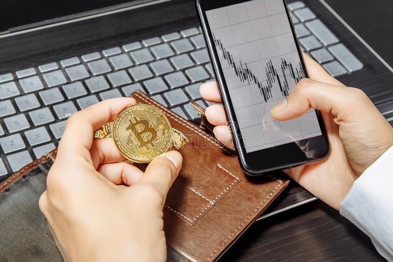 Närbild av händer som rymmer smartphonen och bitcoin Smartphone med den kontanta handeldiagrampå-skärmen Crypto valutabegrepp fin royaltyfri bild