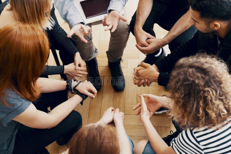 Närbild av händer av tonåringar som sitter i en cirkel under ett supp royaltyfria bilder