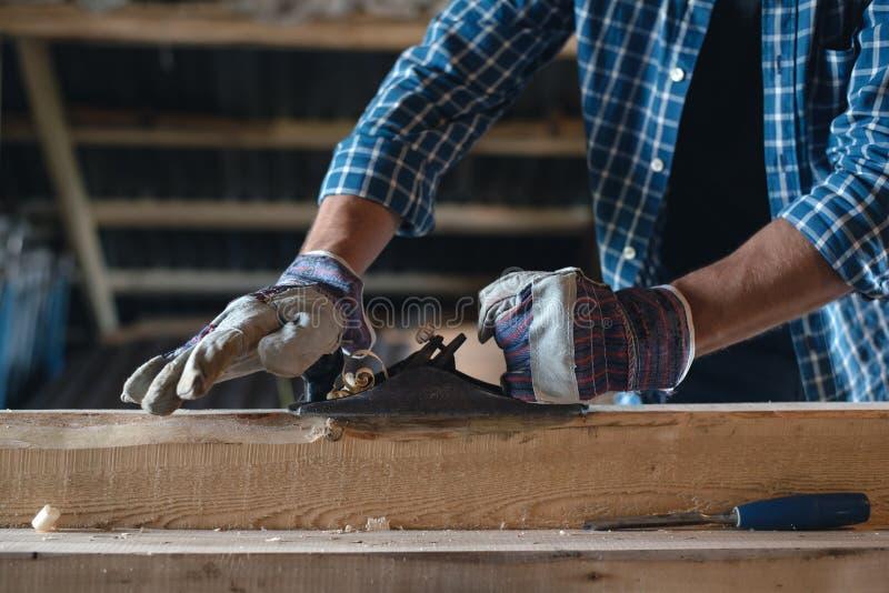 Närbild av händerna för snickare` s i handskar med ett trä för hyvlaremaskinhandtag, manuellt arbete, säkerhet, regler av arbete  royaltyfri fotografi