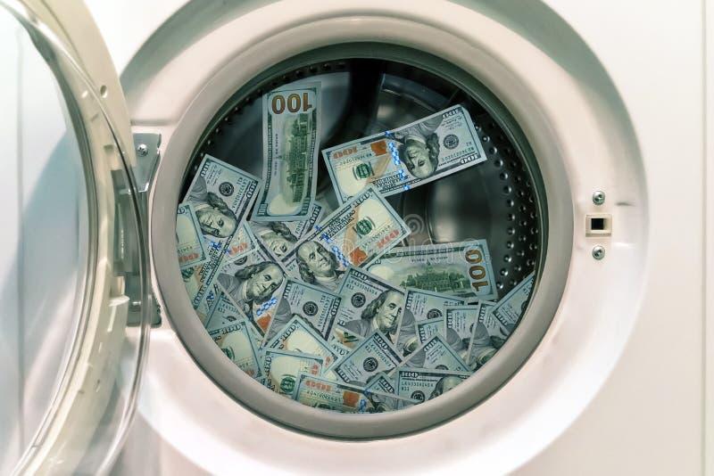 Närbild av högen av smutsiga pengar som förläggas i tvagningmaskin royaltyfri bild