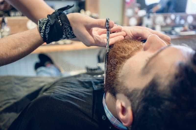 Närbild av handen av en barberare som använder sax, medan klippa t royaltyfri bild