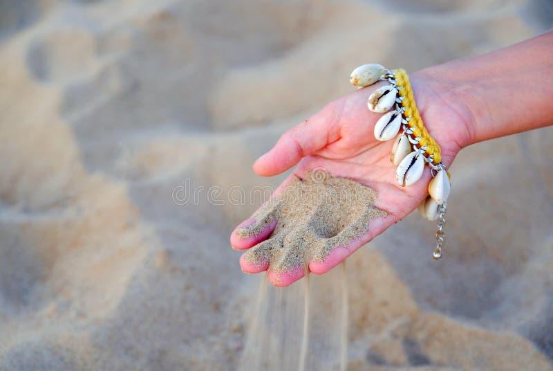 Närbild av handen av en försiktig flicka med ett armband som göras av snäckskal på bakgrunden av vatten Sand igenom arkivbilder