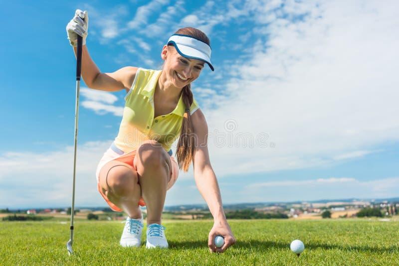Närbild av handen av en kvinnlig spelare som rymmer en boll ovanför golfbanan royaltyfri bild