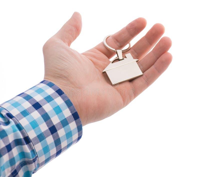 Närbild av handen som ger en nyckel- cirkel med huset som isoleras på vit royaltyfri bild