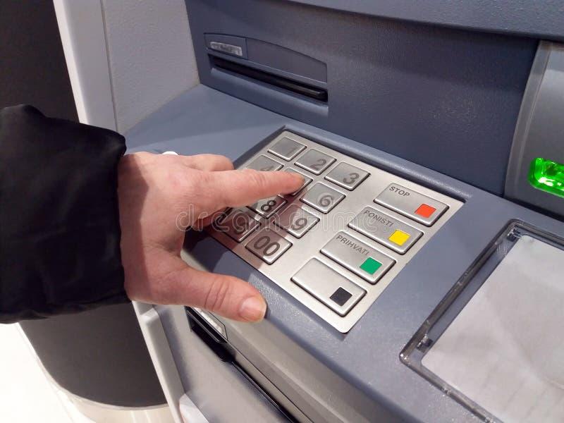 Närbild av handen som skriver in PIN-/passkod på ATM-/bankmaskintangentbord royaltyfri foto