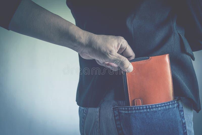 Närbild av handen av tjuven som stjäler plånboken till en kvinna arkivbild