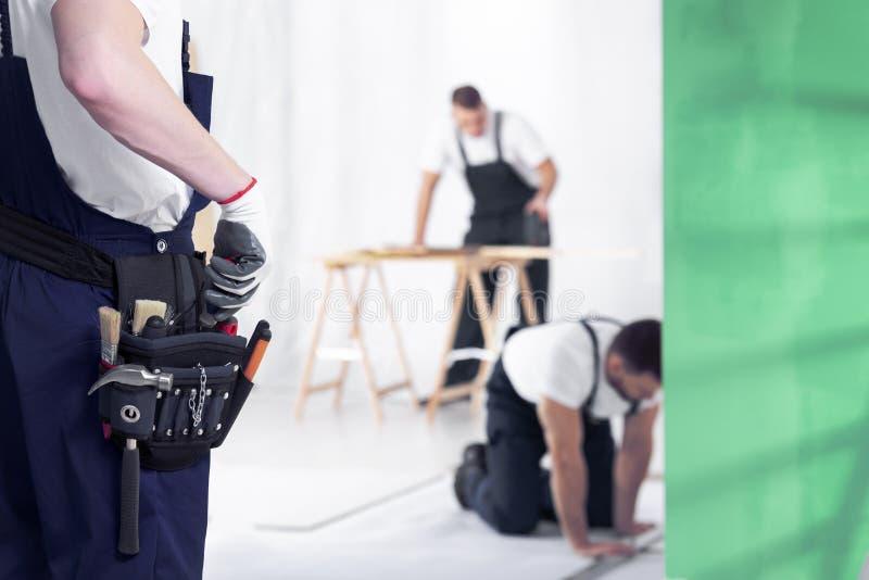 Närbild av hantverkaren med toolbelt under hem- renoveringarbete arkivfoton