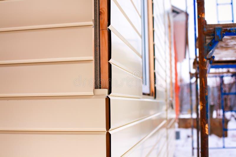 Närbild av hushörnet med beigea sidtäcka väggar och materialet till byggnadsställning arkivbild