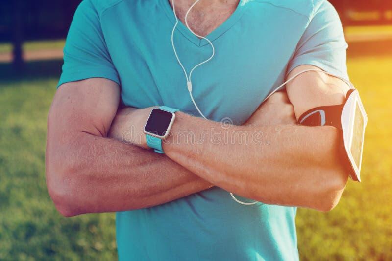 Närbild av idrottsman nenbröstkorgen, den bärande smarta klockan, armbindeln och hörlurar royaltyfri fotografi