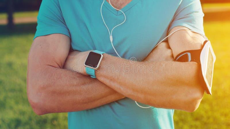 Närbild av idrottsman nenbröstkorgen, med den smarta klockan, armbindeln och hörlurar royaltyfri bild