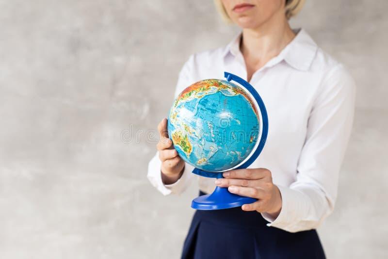 Närbild av jordklotet i händer av den unga kvinnan arkivbild