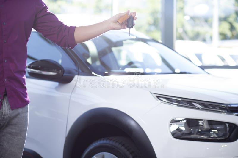 Närbild av köparen med tangenter i hand till den nya exklusiva bilen, i att handla salongen royaltyfria foton