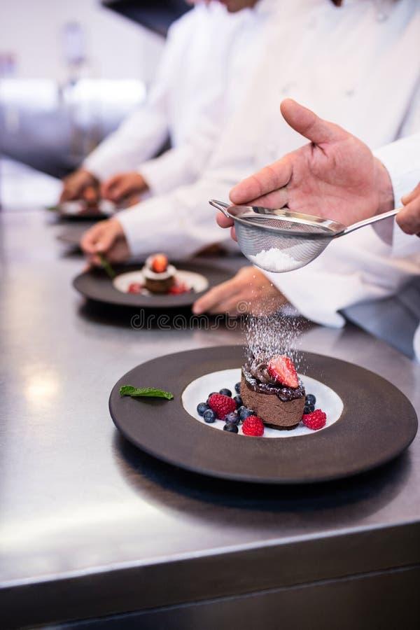 Närbild av kocken som avslutar en efterrättplatta royaltyfria bilder