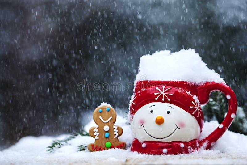 Närbild av koppen med snögubbeframsidan och pepparkakan på snöfall fotografering för bildbyråer