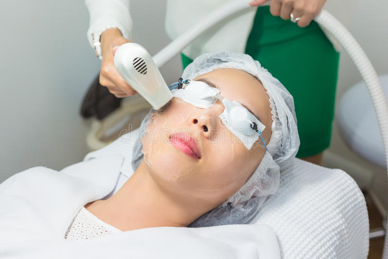 Närbild av kosmetologGiving Laser Epilation behandling till barn arkivfoto
