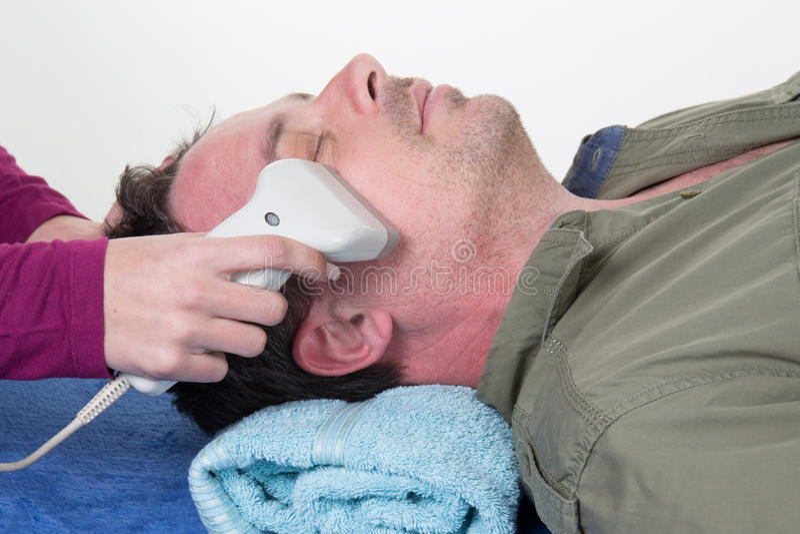 Närbild av kosmetologGiving Laser Epilation behandling till manframsidan royaltyfri bild