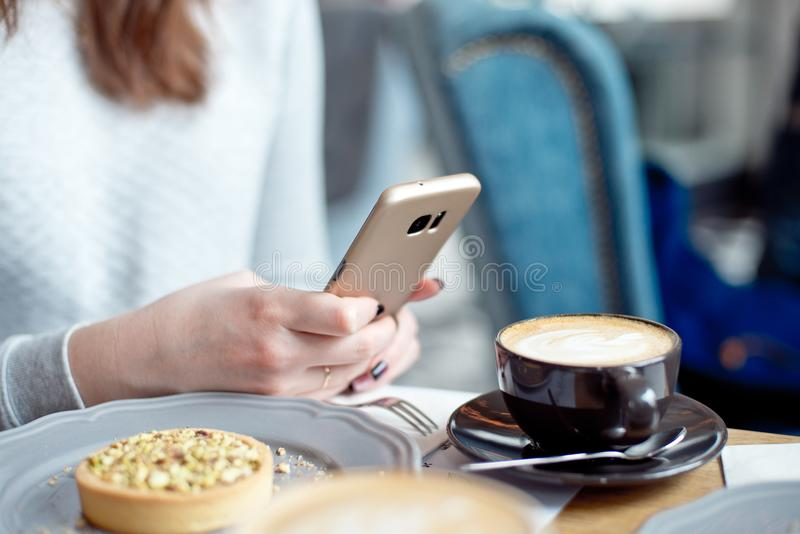 Närbild av kvinnan i hållande mobiltelefon för kafé i hand arkivfoto