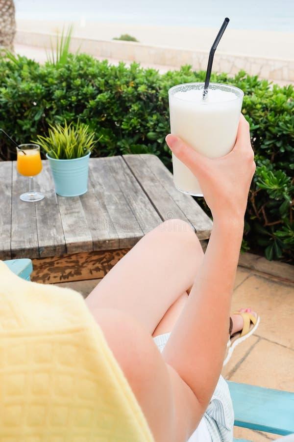 Närbild av kvinnan som rymmer ett exponeringsglas av milkshaken med kokosnöten royaltyfri bild