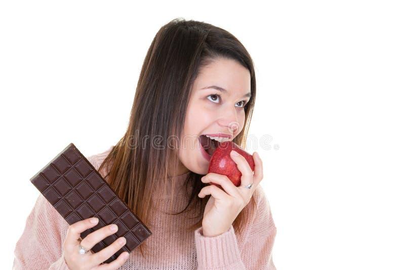 Närbild av kvinnan som visar choklad och äter det röda äpplet royaltyfria foton