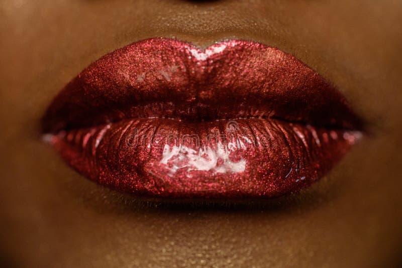 Närbild av kvinnas kanter med ljust modemörker - röd glansig makeup Smink för makrolipglosskörsbär Sexig kyss arkivbild