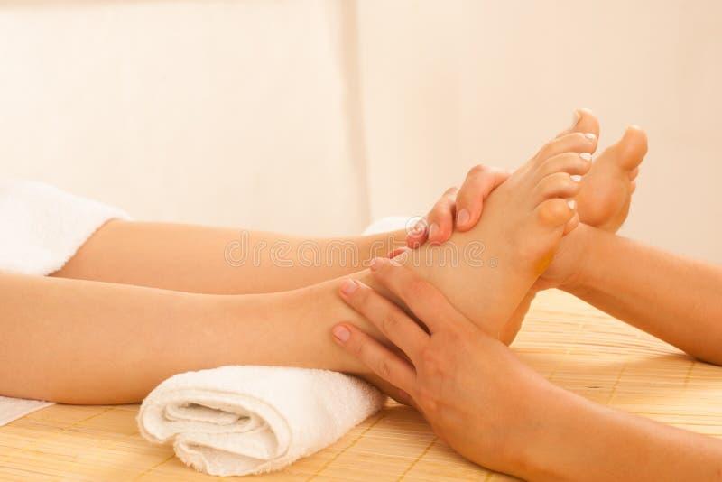 Närbild av kvinnlighänder som gör fotmassage royaltyfri bild