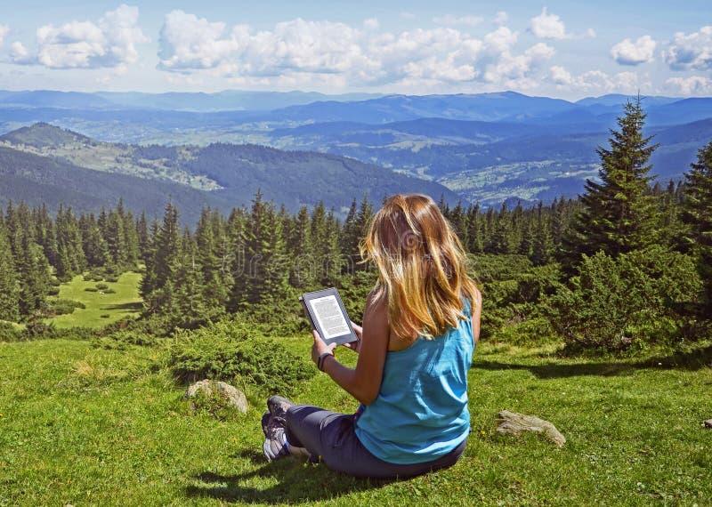Närbild av läs- eBook för kvinna i natur royaltyfri fotografi