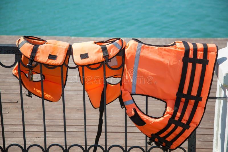 Närbild av Lifejackets på sjön i bakgrunden arkivbild