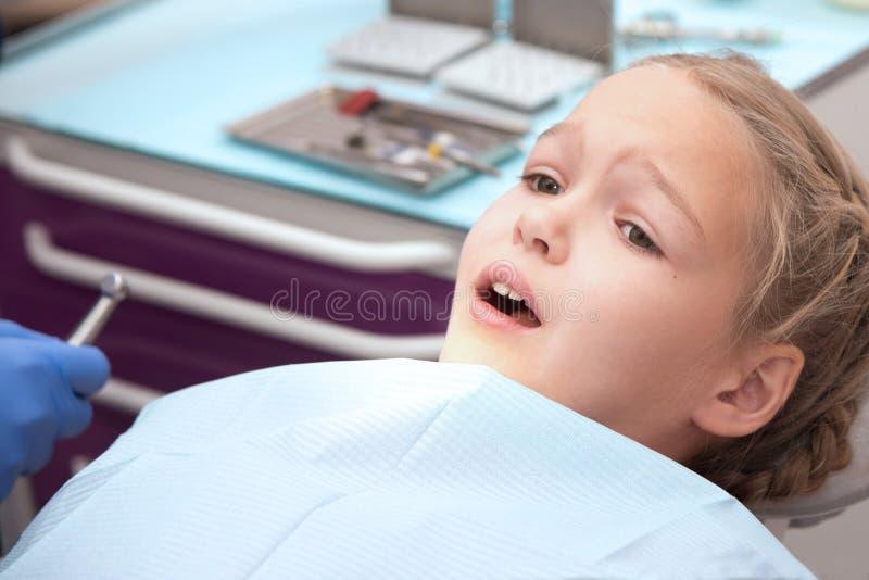 Närbild av lilla flickan som öppnar hennes mun som är bred under kontroll royaltyfri fotografi
