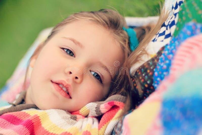 Närbild av lilla flickan som ligger på täcket royaltyfri foto