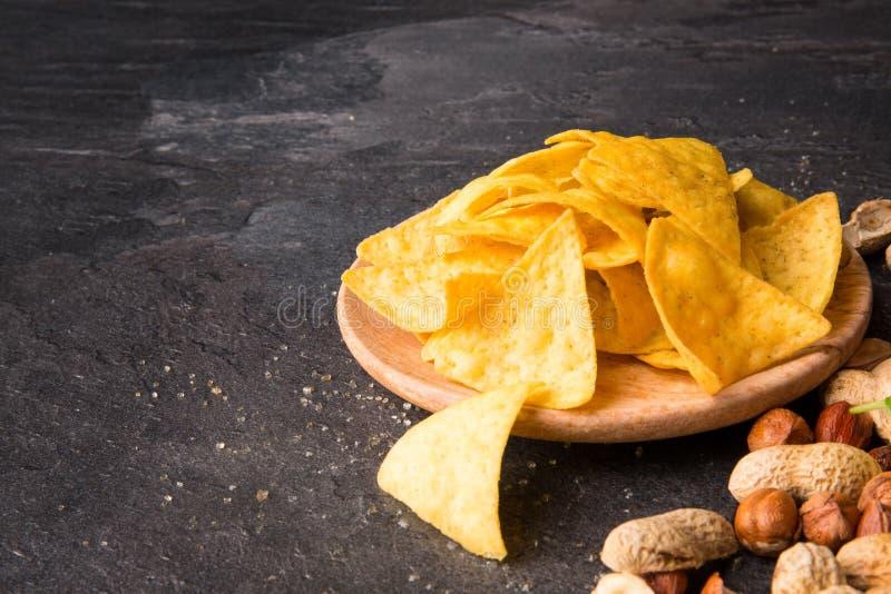 Närbild av ljusa gula nachos på en ljus trärund platta Havrechiper med blandade muttrar på en svart bakgrund arkivbild