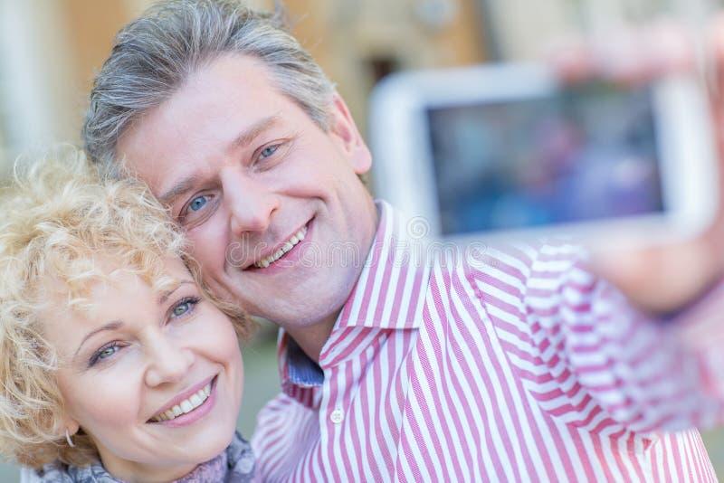 Närbild av lyckliga medelåldersa par som tar selfie till och med den smarta telefonen arkivfoton