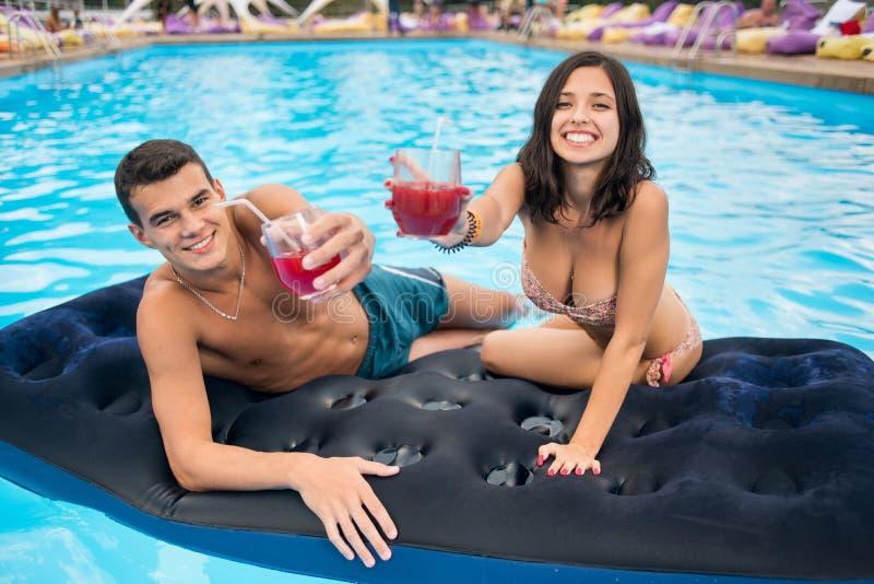 Närbild av lyckliga par med coctailar på madrassen på simbassängen som vänder mot kameran royaltyfria foton