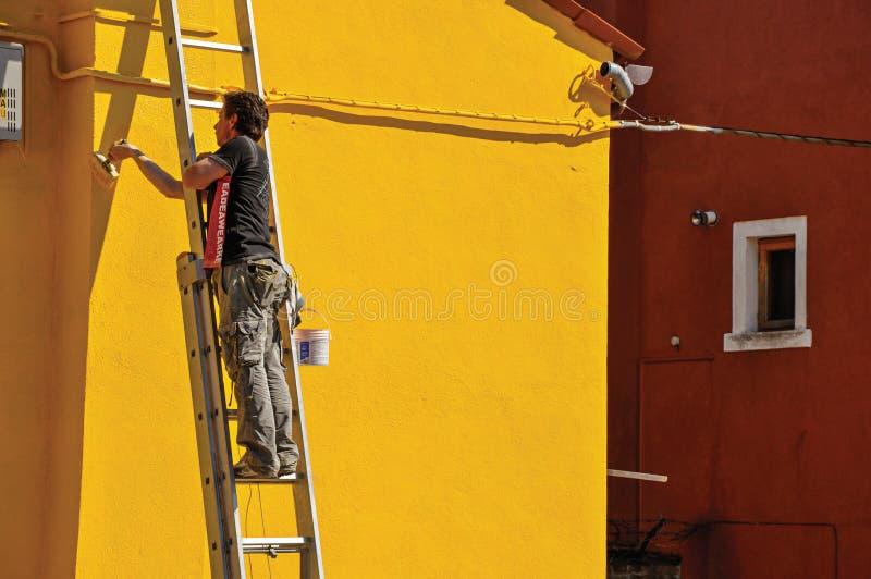 Närbild av målaremålningväggen av huset av guling i Burano royaltyfri fotografi