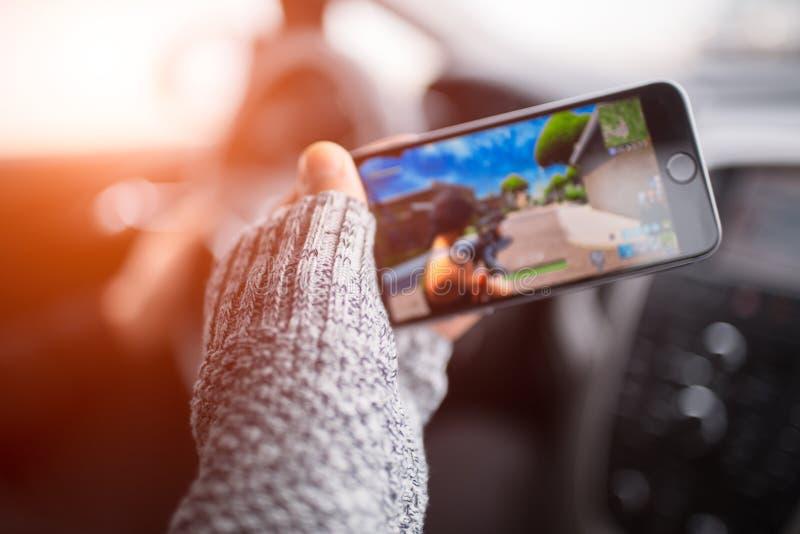 Närbild av manhanden som spelar videospel på smartphonen royaltyfria foton