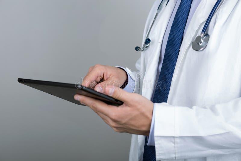 Närbild av manlig doktors PC:n för minnestavla för händer den rörande digitala arkivfoto